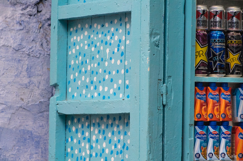 Shop shutters and stocked shelves.