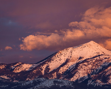 A winter evening with puffy clouds above Box Elder Peak, pink glow across the entire sky lit up the white snow on the mountains below.