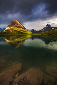 Calm summer morning with spots of sunlight breaking through, on the shore of Swiftcurrent Lake in the Many Glacier region of Glacier National Park.
