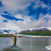 A hiker stands in awe, taking in the beauty of Hallo Glacier and Hallo Lake, inside Katmai National Park, Alaska.