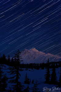 Star trails streak the sky above snow-covered Mt. Shuksan and Picture lake during this long exposure.