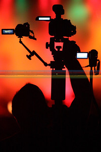 Ween is an open-taping band for audio and video.  This guy has 3 cameras on one large tripod, each pointing to a different part of the stage.  Later, he can mix the 3 together along with the audio tracks, which are recorded separately.