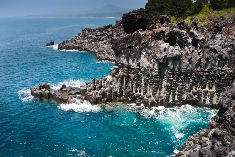 Jejudo Coastline<br /> The Jusangjeolli Cliff. Shot on Jeju Island, South Korea, where 6-sided columns of lava rock rise out of aqua blue water along the Jungman-Daepo Coast. Jeju Island is a honeymoon destination in Asia.