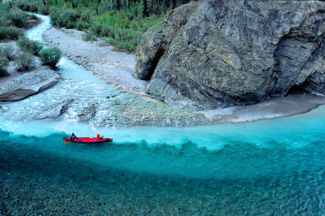 Canoeist paddling past the confluence of the Snake River and Milk Creek - Peel Watershed. The Peel Watershed is located at the northern end of the Rocky and Mackenzie Mountain Chain.