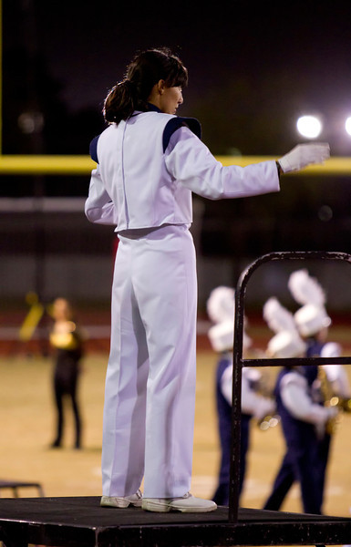 Danielle Chesak, a Drum Major for Coronado High School, conducting on the center podium during the half-time show at Bel Air High School