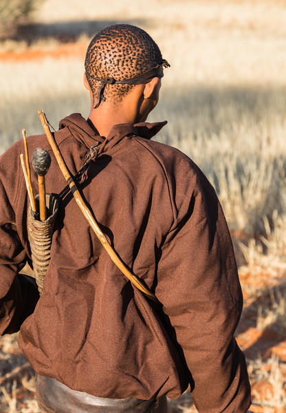 A San man carrying hunting implements