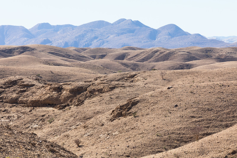 Deserted hills in foreground of tall mountain range
