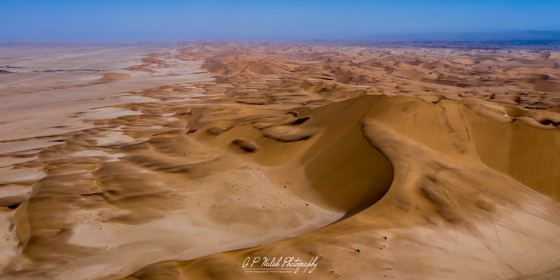 """The Namib Desert is a coastal desert in southern Africa. The name Namib is of Khoekhoegowab origin and means """"vast place"""". According to the broadest definition, the Namib stretches for more than 2,000 kilometres (1,200 mi) along the Atlantic coasts of Angola, Namibia, and South Africa, extending southward from the Carunjamba River in Angola, through Namibia and to the Olifants River in Western Cape, South Africa.  The desert geology consists of sand seas near the coast, while gravel plains and scattered mountain outcrops occur further inland. The sand dunes, some of which are 300 metres (980 ft) high and span 32 kilometres (20 mi) long, are the second largest in the world after the Badain Jaran Desert dunes in China."""
