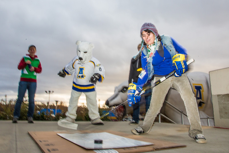 """Elika Roohi tries her hand at a slap shot during festivities surrounding the Starvation Gulch celebration in front of the Patty Center.  <div class=""""ss-paypal-button"""">Filename: LIF-12-3570-032.jpg</div><div class=""""ss-paypal-button-end"""" style=""""""""></div>"""