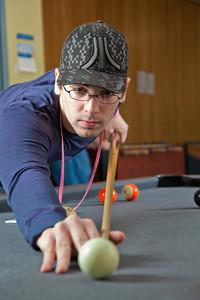Freshman Robert Doerning plays some pool in the Skarland Hall lounge.  Filename: LIF-12-3322-001.jpg