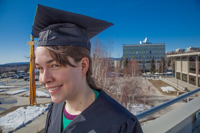 Senior foreign languages major Lindsey Miller poses in her cap and gown on the roof of the Brooks Building on the Fairbanks campus.  Filename: LIF-12-3352-89.jpg