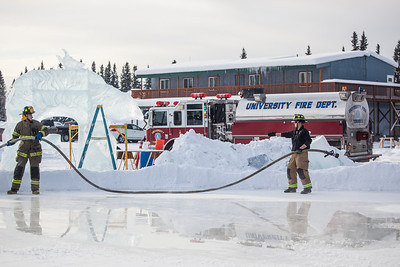 Aaron Stevens and Spencer McLean fill an outdoor ice rink for children at Ice Alaska's George Horner Ice Park in Feb. 2013.  Filename: LIF-12-3723-176.jpg