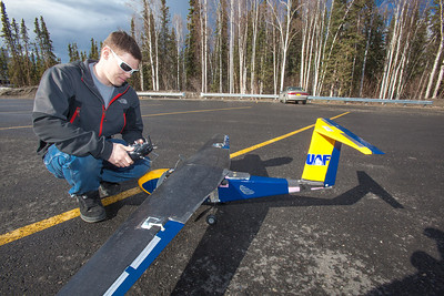 Corey Upton adjusts the remote control of a model plane he helped build and design before sending it aloft for a test flight over a parking lot on the Fairbanks campus.  Filename: LIF-12-3366-016.jpg