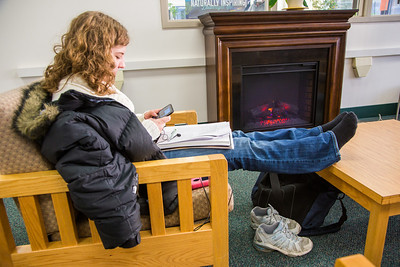 Senior psychology/sociology major Phelicia Wazny relaxes in front of the newly installed fireplace in the Rasmuson Library.  Filename: LIF-13-3711-12.jpg