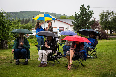 People brave the weather with their umbrellas as they listen to music by the Opera Fairbanks Orchestra Brass at the Georgeson Botanical Garden as part of Summer Sessions' Music in the Garden series.  Filename: LIF-13-3884-39.jpg
