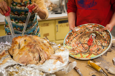 Mary Blurton, and Teresa Shannon carve a turkey before the feasting begins at the annual Thanksgiving gathering at the ceramics department.  Filename: LIF-12-3660-36.jpg