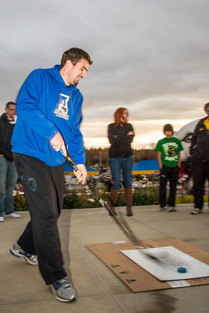 Sergej Pucar tries his hand at a slap shot during festivities surrounding the Starvation Gulch celebration in front of the Patty Center.  Filename: LIF-12-3570-053.jpg