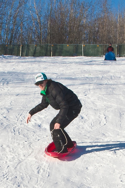"""Jimmy Donohue surfs down the sledding hill on campus.  <div class=""""ss-paypal-button"""">Filename: LIF-12-3289-24.jpg</div><div class=""""ss-paypal-button-end"""" style=""""""""></div>"""