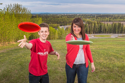 Friends Aaron Druyvestein and Serena McCormick enjoy a round of disc golf on the campus course near the University of Alaska Museum of the North.  Filename: LIF-14-4191-156.jpg