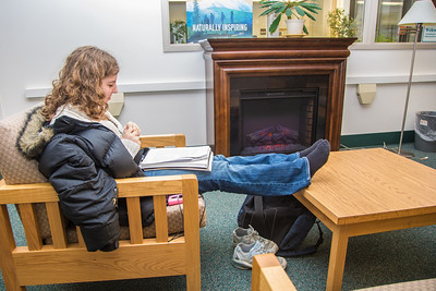 Senior psychology/sociology major Phelicia Wazny relaxes in front of the newly installed fireplace in the Rasmuson Library.  Filename: LIF-13-3711-8.jpg