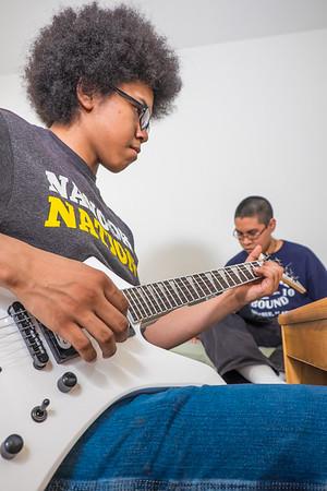 Terrell Jones, a computer science major from Deering, practices guitar in his room in the Eileen Panigeo MacLean House, while his roommate Ivik Henry surfs the Internet.  Filename: LIF-15-4463-147.jpg