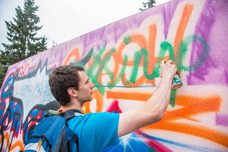 """Shaun Nesheim leaves a contribution on the free speech wall erected each fall by ASUAF in front of the Wood Center.  <div class=""""ss-paypal-button"""">Filename: LIF-12-3555-05.jpg</div><div class=""""ss-paypal-button-end"""" style=""""""""></div>"""