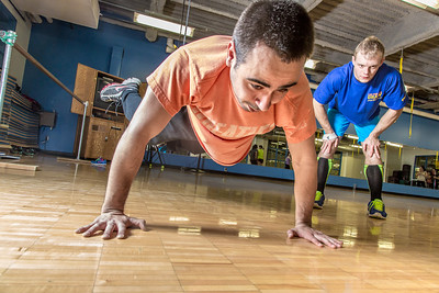 Gavin Meggert, a personal trainer at the SRC, helps supervise Aaron Orr on his fitness routine during a workout session.  Filename: LIF-14-4111-40.jpg