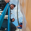 """Art major Bryson DeRonde lends a helping hand during the installation of a yurt set up next to the outdoor climbing wall by the SRC. The structure will serve as a warm-up hut and to store safety gear.  <div class=""""ss-paypal-button"""">Filename: LIF-12-3287-06.jpg</div><div class=""""ss-paypal-button-end"""" style=""""""""></div>"""