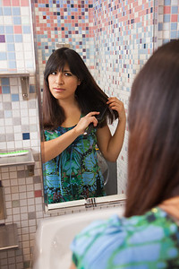 Skarland Hall resident Sara Spindler brushes her hair in one of the dorm's newly re-modeled bathrooms.  Filename: LIF-12-3322-141.jpg