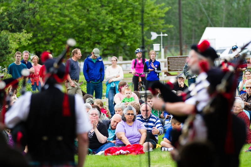 """Scores of people listen to the Red Hackle Pipe Band during the kick-off event of Summer Sessions' Music in the Garden Series at the Georgeson Botanical Garden.  <div class=""""ss-paypal-button"""">Filename: LIF-12-3426-6.jpg</div><div class=""""ss-paypal-button-end"""" style=""""""""></div>"""