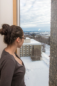 A resident of Moore Hall checks out the view from the 8th floor on a winter afternoon.  Filename: LIF-13-3735-189.jpg