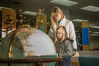 Jaimee Coon points out some features on the globe while visiting the Rasmuson Library with her third grade daughter Amaya.  Filename: LIF-14-4045-105.jpg