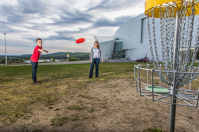 Friends Aaron Druyvestein and Serena McCormick enjoy a round of disc golf on the campus course near the University of Alaska Museum of the North.  Filename: LIF-14-4191-29.jpg