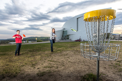 Friends Aaron Druyvestein and Serena McCormick enjoy a round of disc golf on the campus course near the University of Alaska Museum of the North.  Filename: LIF-14-4191-27.jpg