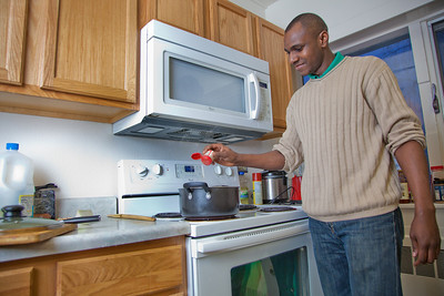 Peter Ikewun, a petroleum engineeering graduate student from Nigeria, prepares a traditional African soup in his communal Wickersham Hall kitchen.  Filename: LIF-12-3268-023.jpg