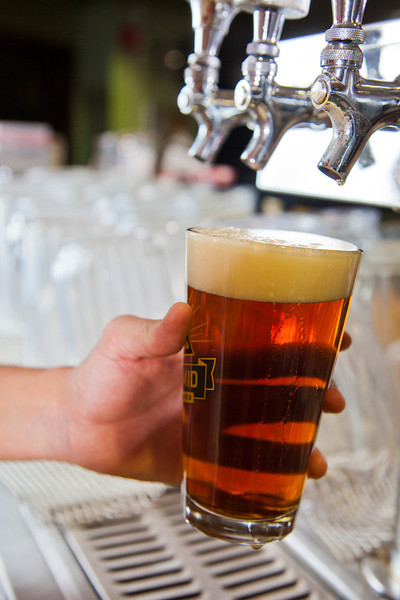 """Ida Petersen attempts to draw the perfect draft beer during her shift as a server in UAF's Wood Center Pub.  <div class=""""ss-paypal-button"""">Filename: LIF-11-3217-054.jpg</div><div class=""""ss-paypal-button-end"""" style=""""""""></div>"""