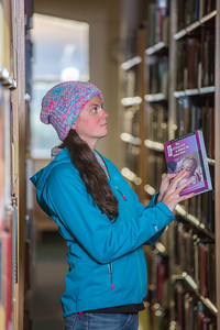 Senior biology major Sarah Dewitt looks through the stacks on the 6th floor of the Rasmuson Library.  Filename: LIF-14-4045-134.jpg