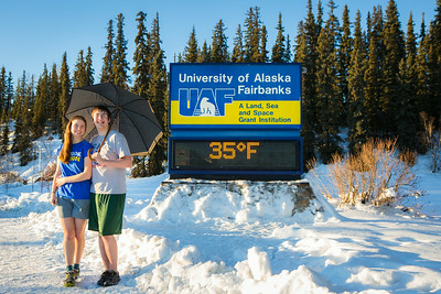 Sporting shorts and a t-shirt in above freezing temperatures in January, Megan Lasselle and Seth Reddell pose for a portrait at the time and temperature sign.  Filename: LIF-14-4047-38.jpg