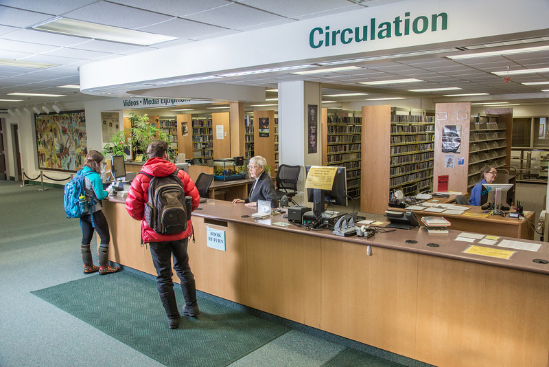 "Students check out materials from circulation desk at the UAF Rasmuson Library on the Fairbanks campus.  <div class=""ss-paypal-button"">Filename: LIF-14-4045-150.jpg</div><div class=""ss-paypal-button-end"" style=""""></div>"