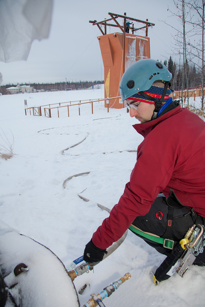 """UAF Outdoor Adventures volunteer Jason Thies turns on the water as colleagues atop the new climbing tower start the spray to form the foundation for ice climbing.  <div class=""""ss-paypal-button"""">Filename: LIF-11-3246-07.jpg</div><div class=""""ss-paypal-button-end"""" style=""""""""></div>"""