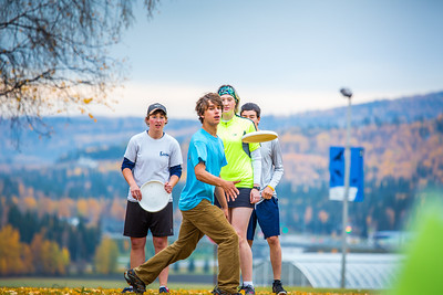 Students warm up for a bout of utlimate frisbee in the field near the University of Alaska's Museum of the North on a fall afternoon.  Filename: LIF-12-3557-056.jpg