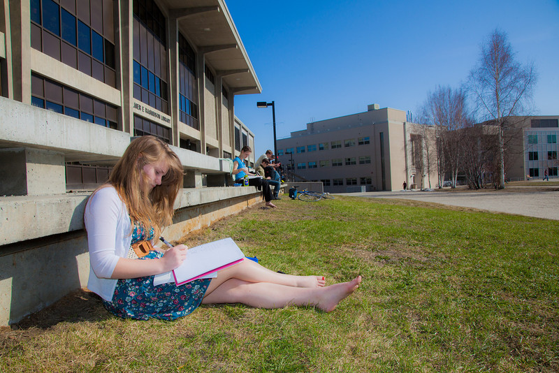 """UAF student Kaylee Miltersen works on her homework in the April sunshine outside the library.  <div class=""""ss-paypal-button"""">Filename: LIF-12-3356-78.jpg</div><div class=""""ss-paypal-button-end"""" style=""""""""></div>"""