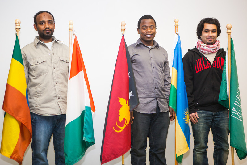 """Students from left, Abraham Endalamaw of Ethiopia, Bertrand Dushime of Rwanda and Fahad Alshamman of Saudi Arabia stand beside the flags representing their country after a dedication ceremony at the Wood Center.  <div class=""""ss-paypal-button"""">Filename: LIF-12-3655-59.jpg</div><div class=""""ss-paypal-button-end"""" style=""""""""></div>"""