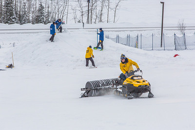 Student employees and staff members work to groom the big jump on UAF's Terrain Park on a snowy spring afternoon.  Filename: LIF-13-3721-1.jpg