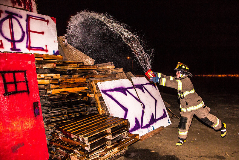"A student with the University Fire Department douses one of the bonefire structures with gasoline moments before they were torched during traditional Starvation Gulch activities Sept. 29.  <div class=""ss-paypal-button"">Filename: LIF-12-3571-074.jpg</div><div class=""ss-paypal-button-end"" style=""""></div>"