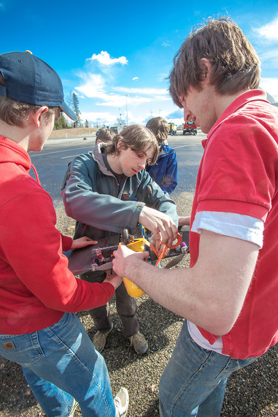"""Sam Brewer, center, and other engineering majors tinker with their model plane before sending it aloft for a test flight over a parking lot on the Fairbanks campus.  <div class=""""ss-paypal-button"""">Filename: LIF-12-3366-025.jpg</div><div class=""""ss-paypal-button-end"""" style=""""""""></div>"""
