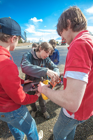 Sam Brewer, center, and other engineering majors tinker with their model plane before sending it aloft for a test flight over a parking lot on the Fairbanks campus.  Filename: LIF-12-3366-025.jpg