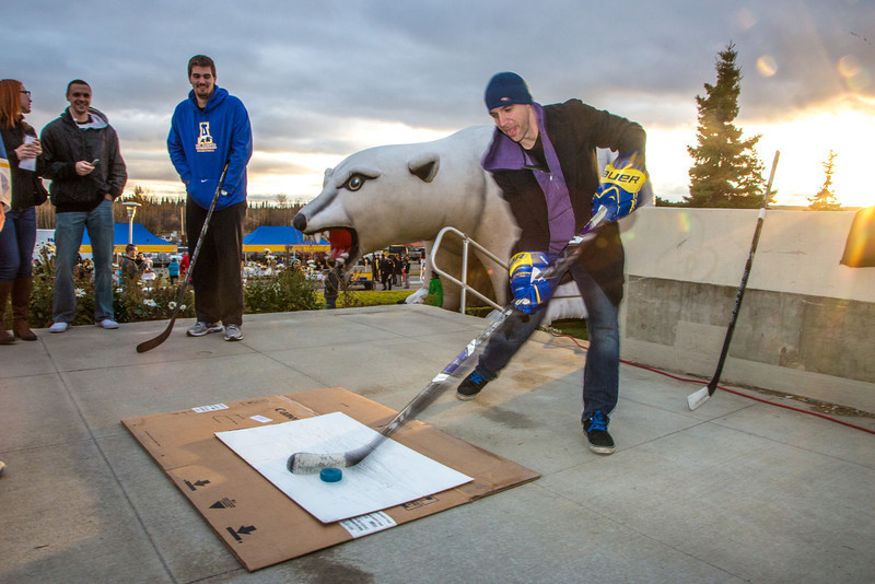 "Nanook supporter Greg Kreta tries his hand at a slap shot during festivities surrounding the Starvation Gulch celebration in front of the Patty Center.  <div class=""ss-paypal-button"">Filename: LIF-12-3570-070.jpg</div><div class=""ss-paypal-button-end"" style=""""></div>"