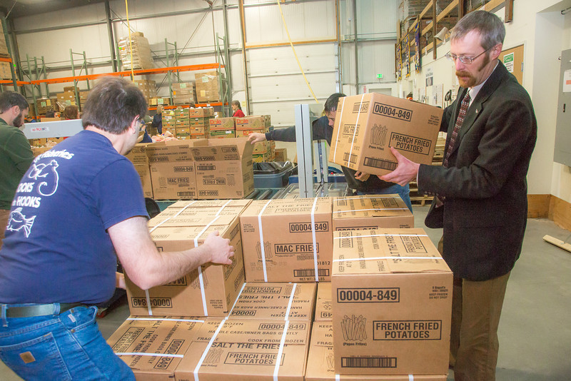 """SFOS IT manager John Haverlack, left, and Institute of Northern Engineering Director Dan White load boxes onto pallets for delivery around Fairbanks while volunteering at the Fairbanks Community Food Bank.  <div class=""""ss-paypal-button"""">Filename: LIF-12-3661-25.jpg</div><div class=""""ss-paypal-button-end"""" style=""""""""></div>"""