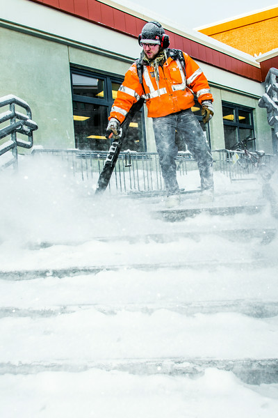 "A groundskeeper on the Facilities Services crew clears campus steps and sidewalks after a February morning snowfall.  <div class=""ss-paypal-button"">Filename: LIF-14-4072-22.jpg</div><div class=""ss-paypal-button-end""></div>"